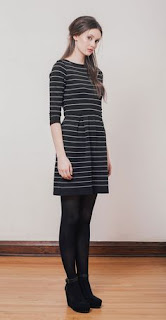A woman in a black horizontally-striped dress in black leggings and boots