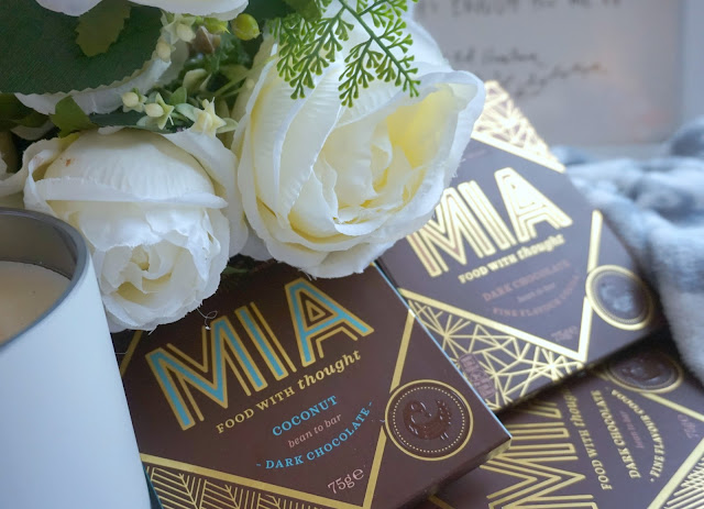 bars of MIA chocolate, white flowers and a candle