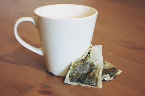 a mug of green tea sitting on a kitchen table, with two used green tea bags placed next to the mug on the table