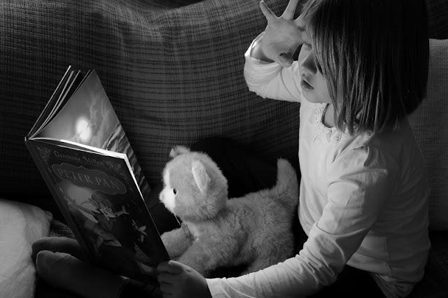 Ritratto di una bambina che racconta una storia al suo peluche