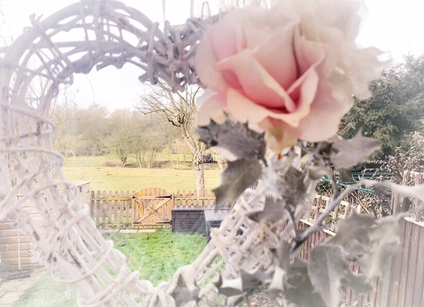 White wicker heart with a view to a garden