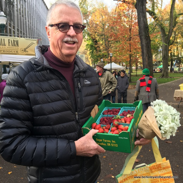 happy shopper with season's last strawberries at Portland Farmers Market in Portland, Oregon