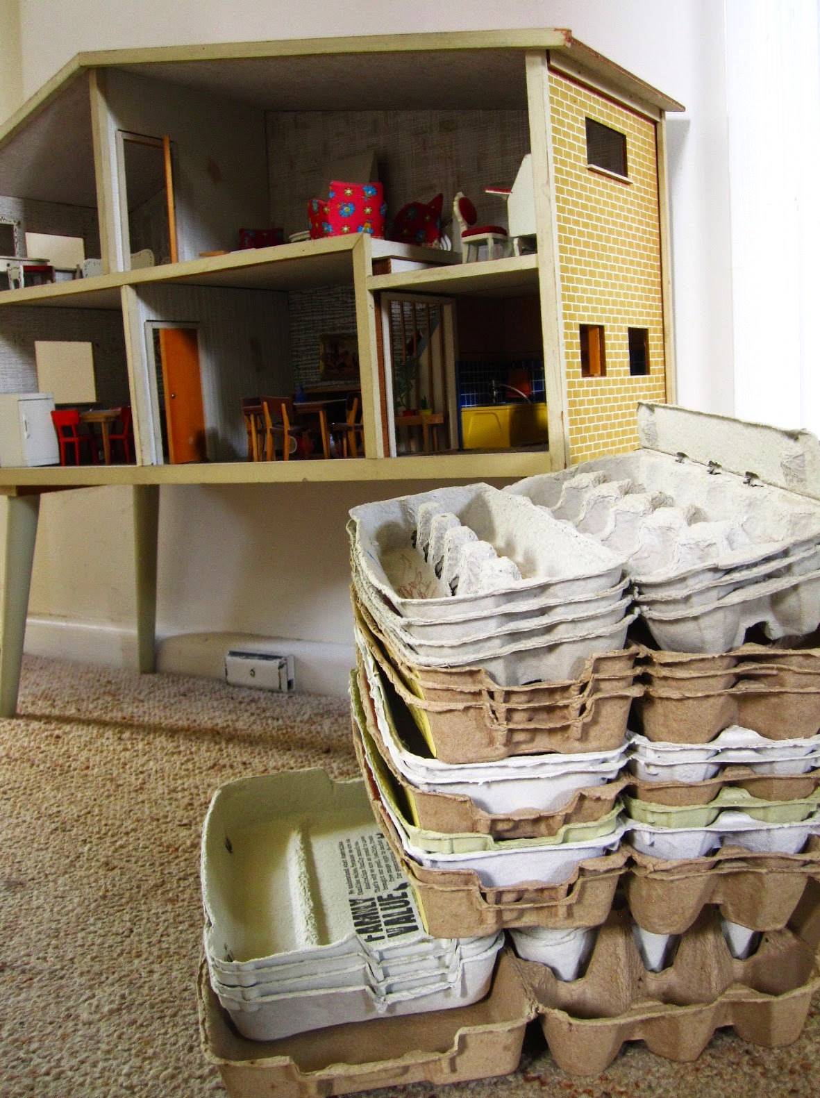 A stack of empty egg cartons in front of a vintage Lundby dolls' house.