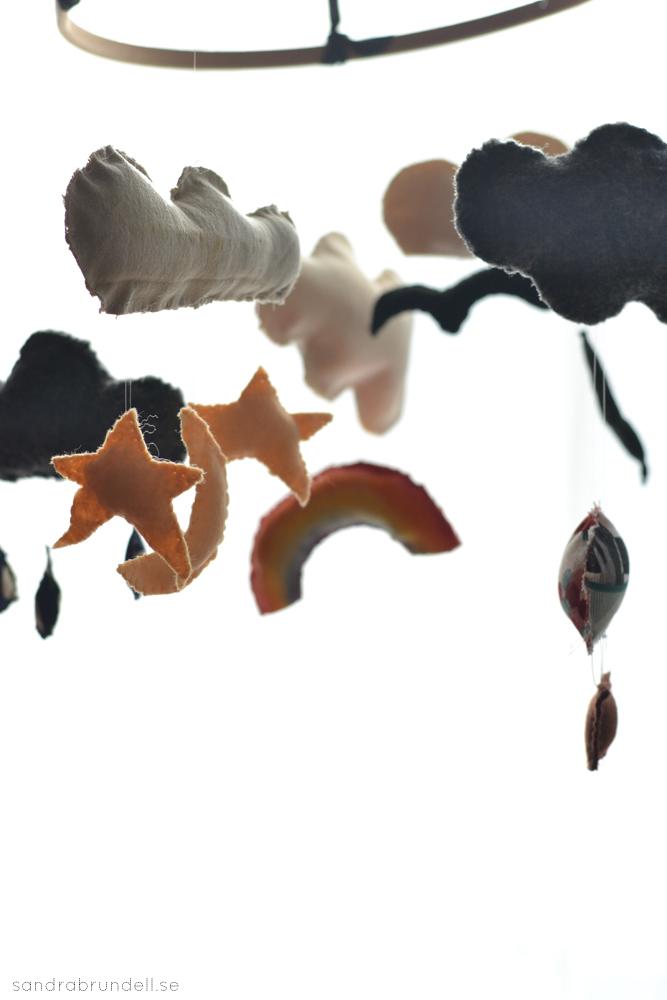 Sy en mobil till spjälsängen med moln och stjärnor, måne, regnbåge, fåglar, regndroppar och luftballong.