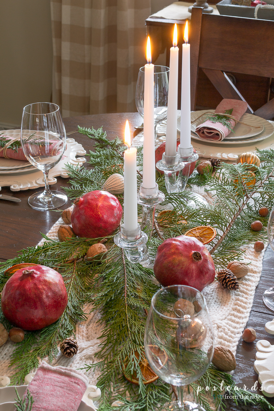 dining room table center piece with glass candleholders and cypress branches