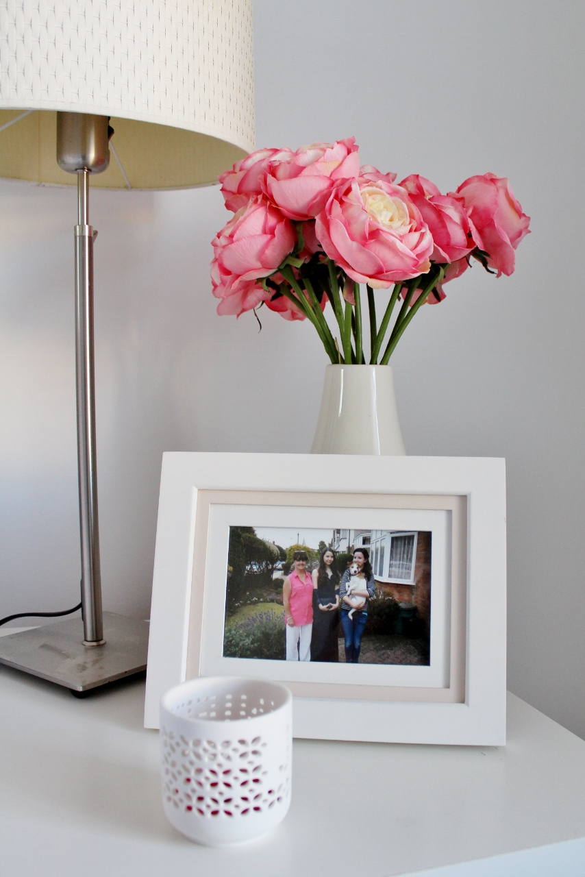 Pink peonies, candle and photo frame on bedside table