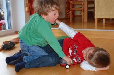 Zwei Kinder schlagen sich und liegen am Boden