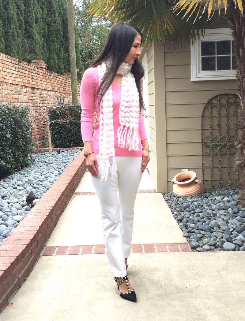 Wearing pink sweater with white pants and white winter scarf.