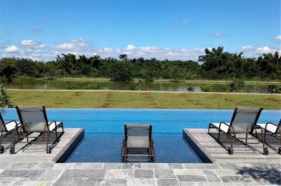 A piscina, de borda infinita, oferece visão para um lago com mata ciliar.