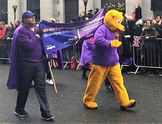 Pic of man dressed in bear costume with banner-carriers for polio behind him