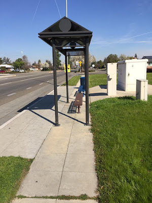 A bus shelter on a quiet street, there is blue sky with bright sun and green grass
