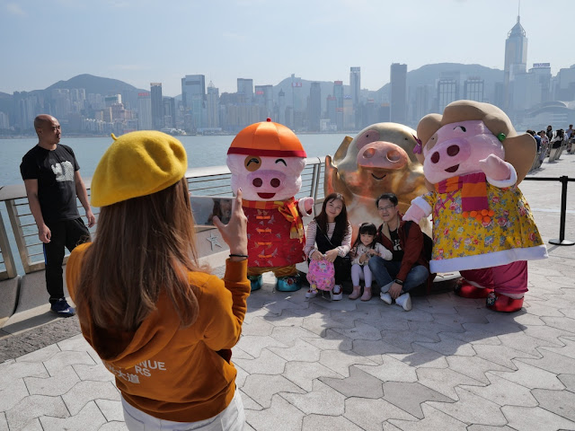 Family being photographed with a sculpture of the pig cartoon character McDull at the Avenue of the Stars