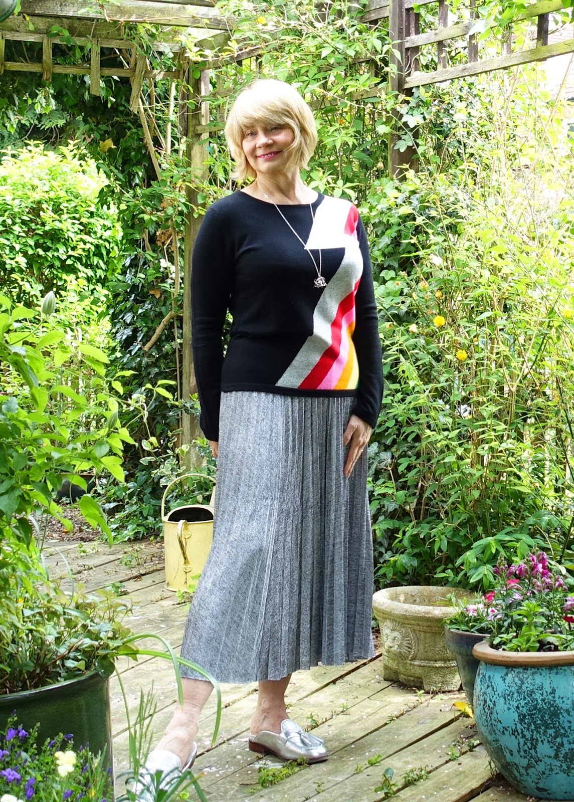 Woman wearing a black jumper with a Bowie style rainbow stripe and silver pleated skirt