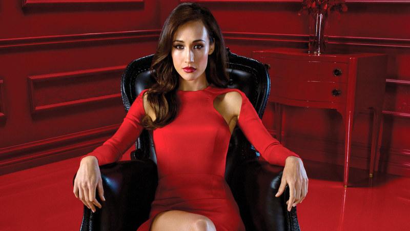 Nikita, de vestido vermelho, sentada em uma poltrona