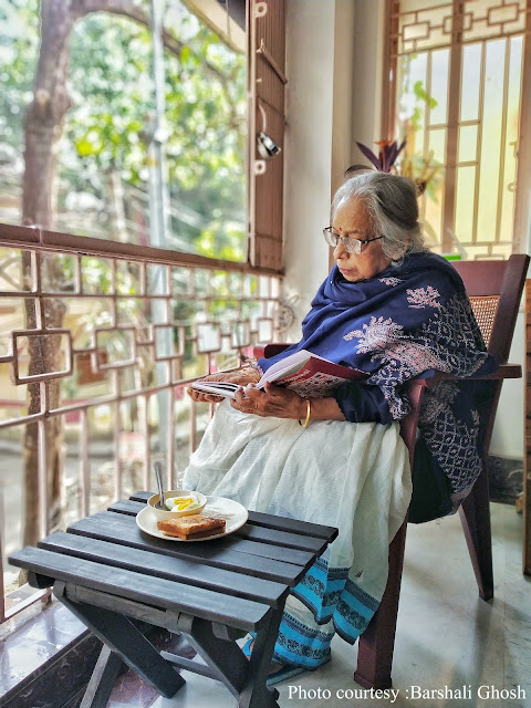 Mrs Sen in the balcony, reading a book to herself.