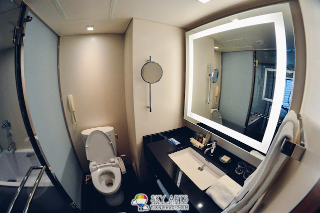 A toilet with square size well illuminated mirror and automatic toilet bowl at Hilton Tokyo