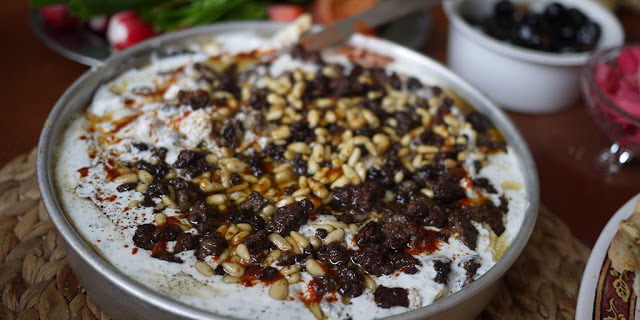 Chicken Fatteh in a serving dish Garnished with sauteed pine nuts