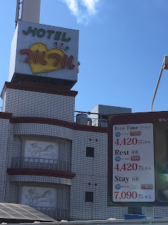 A picture of a love hotel with prices listed outside for long and short stays