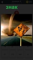 На дороге сбоку установлен знак опасности и вдали виднеется торнадо с воронкой