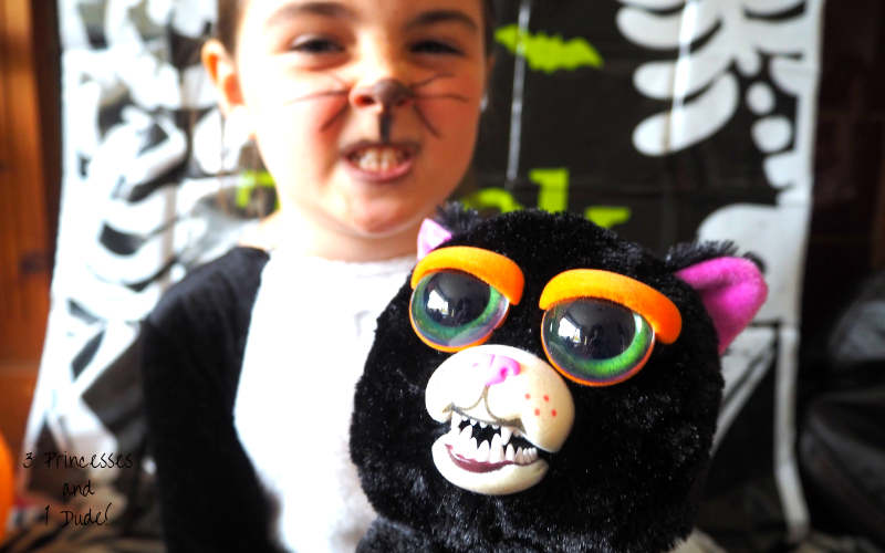 A young girl dressed in a black and white Halloween cat costume, with dimante cat ears and a face painted nose and drawn on whiskers is pulling a snarly face whilst holding a Feisty Pet Cranky Cathy, a 25cm soft toy, the toy is black with big doe eyes, cartoonish orange eyebrows, a white mouth and sharp snarly teeth.