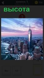В середине огромного города на побережье стоит высокий небоскреб в свете заката