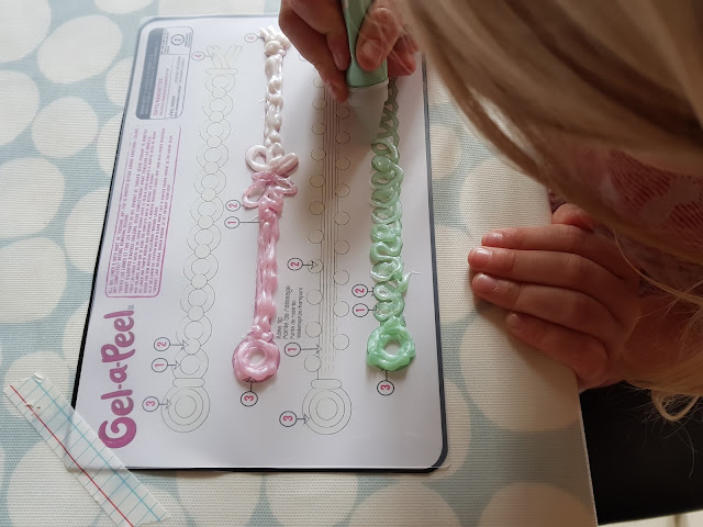 A close up of a gel-a-peel template with a young girl squeezing the gel out to create a bracelet