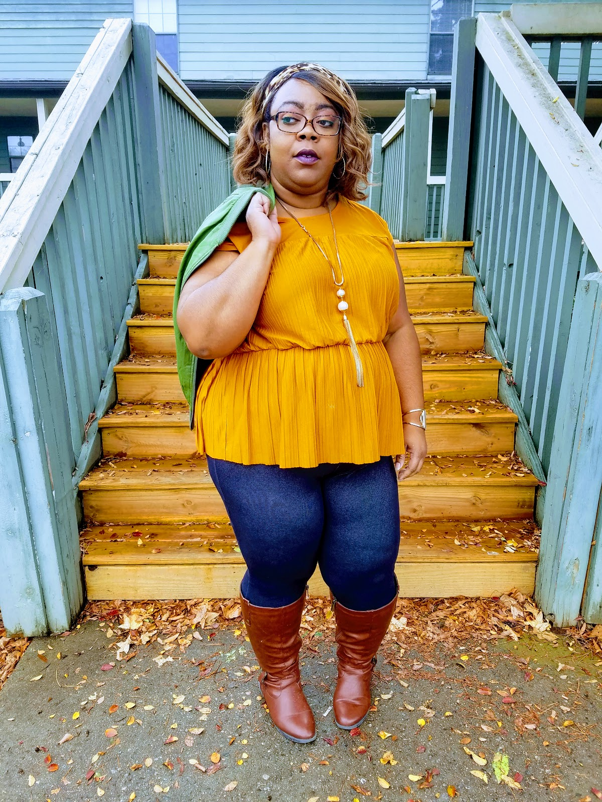 Curvy blogger with mustard blouse, green bomber jacket, denim jeggings, cognac boots