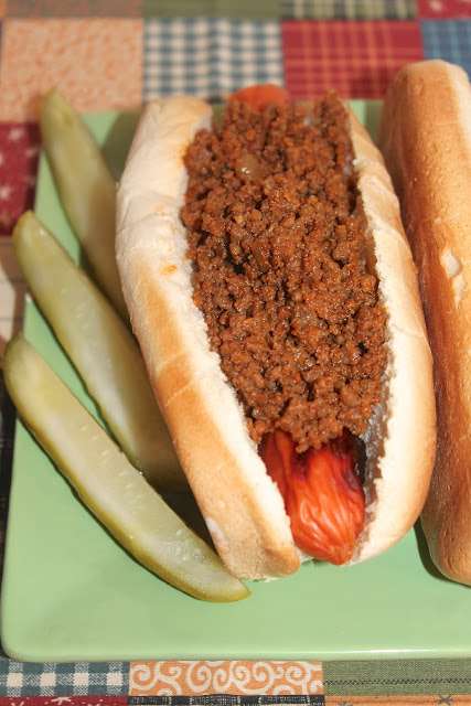 Close-up of a finished hot dog topped with the finished hot dog sauce.