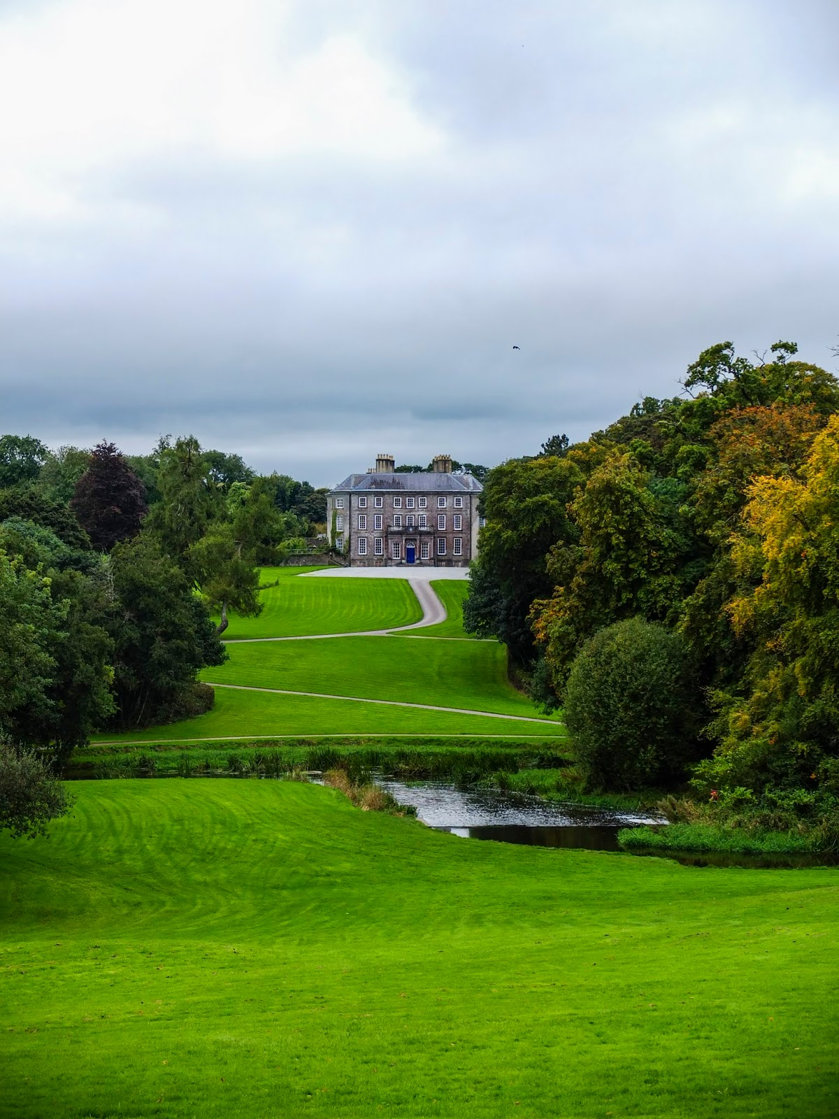 A view of the Doneraile House across the green grounds.