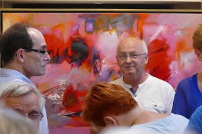 Profesor historii sztuki na tle czerwonego obrazu abstrakcyjnego, wernisaż malarstwa w galerii Wieża Sztuki