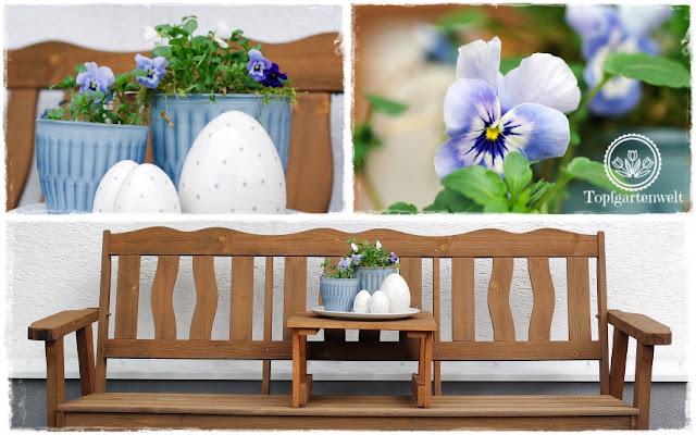 Gartenblog Topfgartenwelt Osterdeko: eine Gartenbank geschmückt mit pastellblauen Töpfen, Hornveilchen und Porzellaneiern