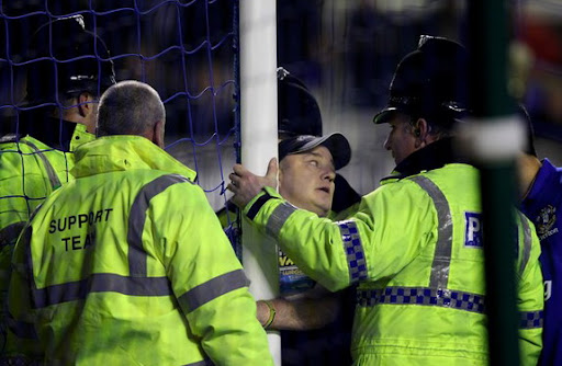 Police speak to a man who handcuffed himself to the goalpost