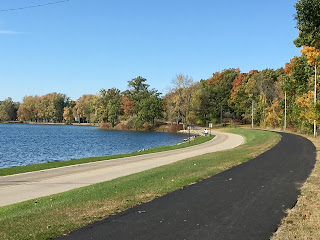 paved asphalt road nearwalking path and  lake with fall colors