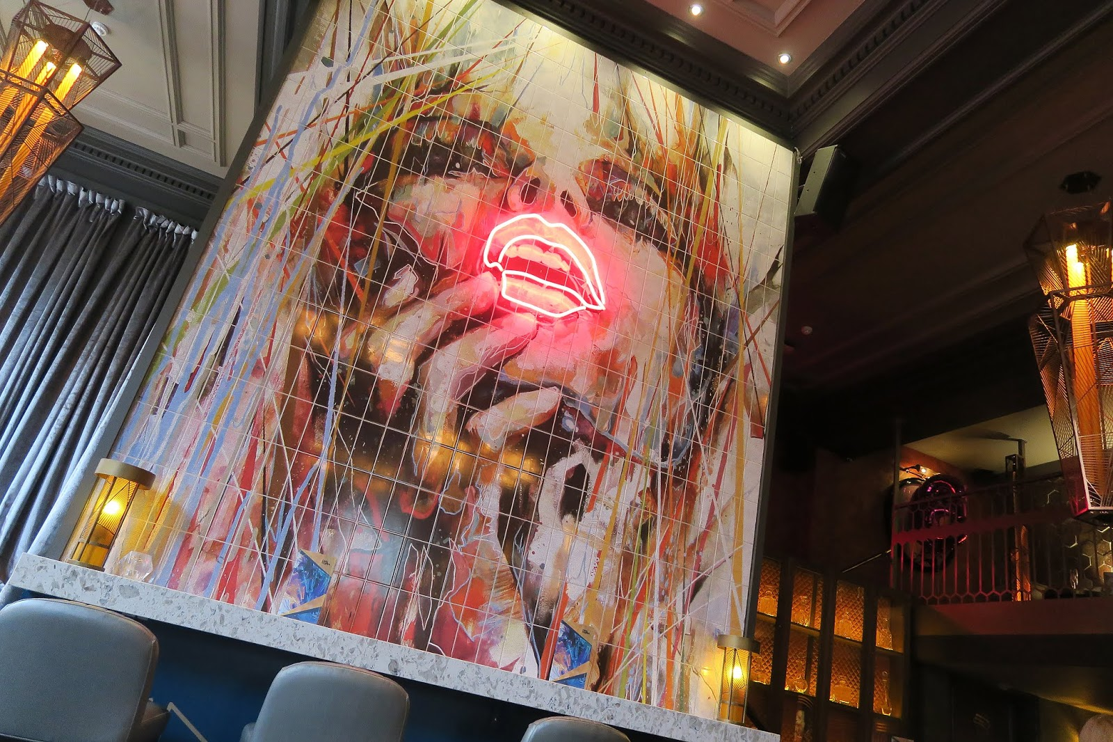 HUGE MURAL OF A WOMAN INSIDE DIRTY MARTINI BIRMINGHAM. THE WOMANS LIPS ARE LIT UP WITH A NEON LIGHT