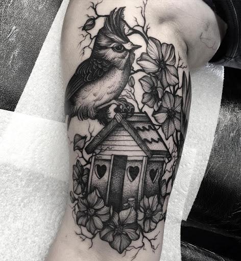 Um bonito e muito sleeve tatuagem. Os tons de cinza da tatuagem combina com o design perfeitamente. Você pode ver um pássaro empoleirado em uma casa de passarinho que parece estar-se em uma árvore repleta de flores. Tudo adorável combinados em apenas um projeto.