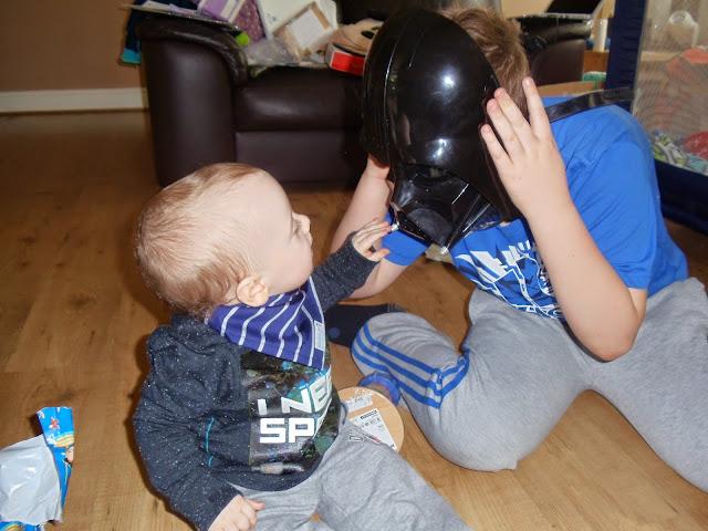little boy reaching out to an older boy wearing a darth vader helmet