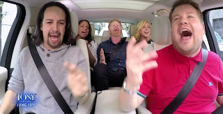 Corden and guests in car, all with mouths open while singing and gesturing