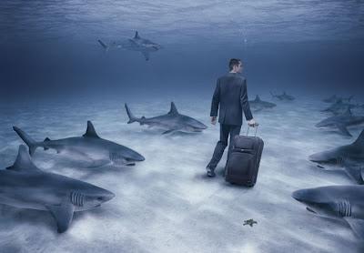 fotomontaje ejecutivos en el fondo del mar con male maleta y tiburones al asecho
