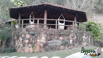 Muro de pedra com pedras rústicas na construção do quiosque de telhas com eucalipto tratado, com o corrimão de madeira, o guarda corpo em cima do muro de pedra em sítio em Atibaia-SP.
