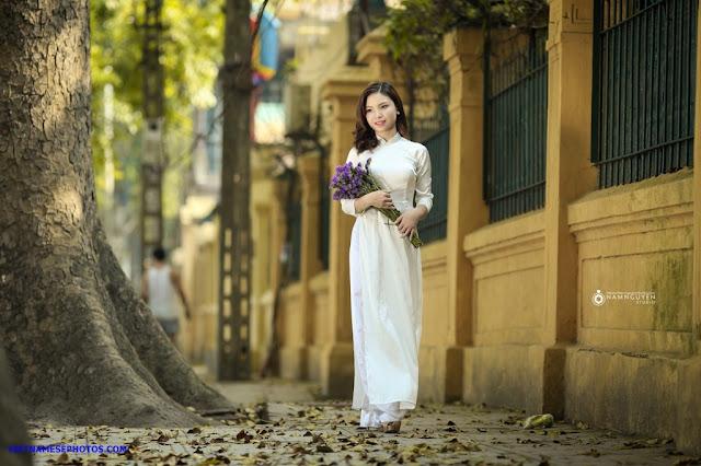 Vietnamese teen girl walking on the street with white ao dai 4