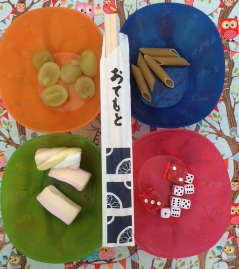 Pair of chopsticks, laid over four bowls containing grapes, uncooked pasta, marshmallows and dice