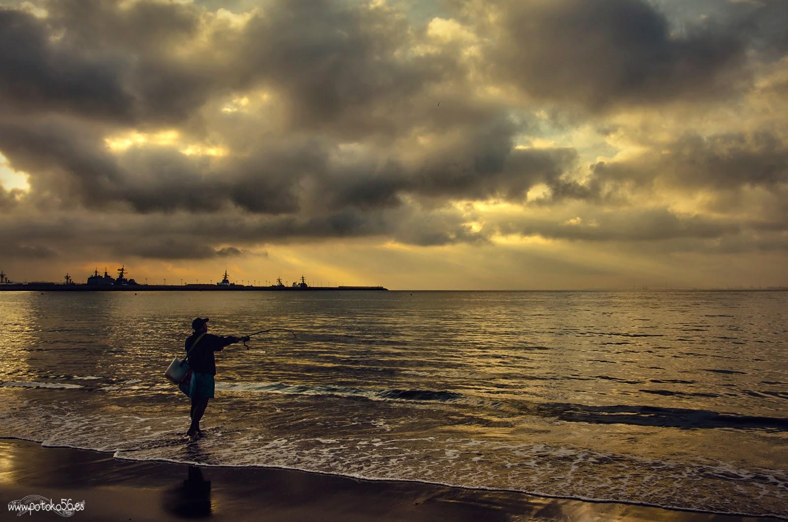 Playa del Chorrillo Rota con una variedad de nubes y un pescador en la orilla
