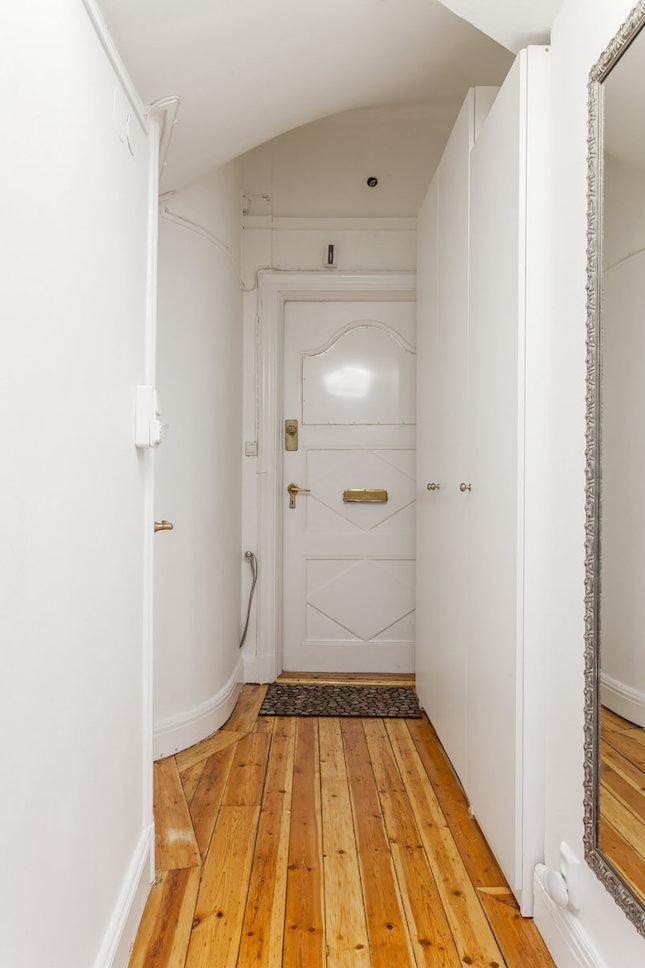 Puerta blanca de entrada de un piso pequeño