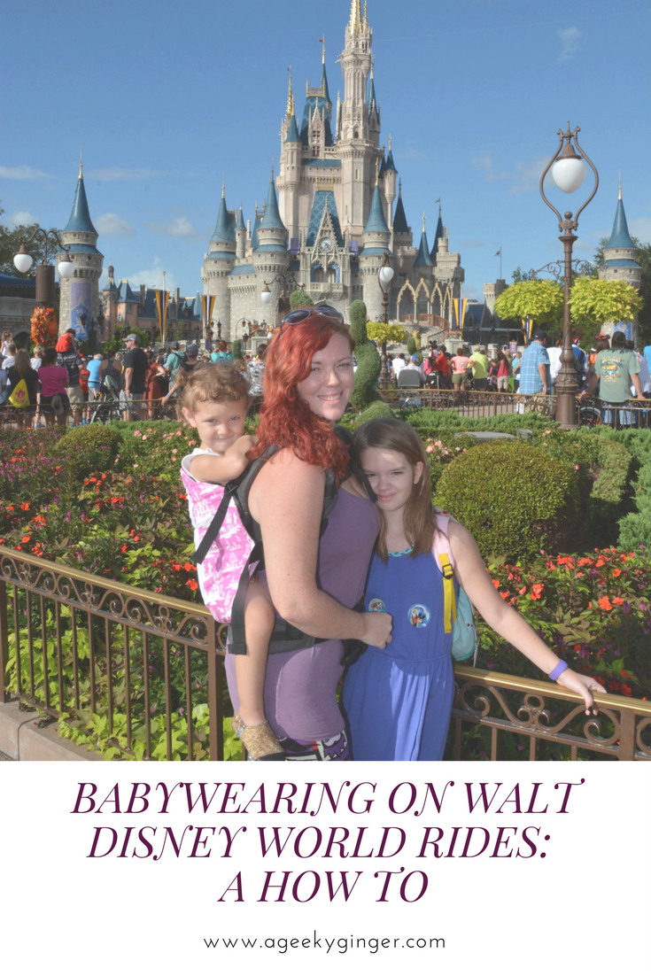 "A curly red haired mom in a purple tank top is looking at the camera. She is babywearing her toddler in a pink soft structured carrier on her back. Her older daughter is standing in front of her, facing the camera, and is wearing a long blue dress. They are in front of Cinderella's Castle and the Magic Kingdom. The caption reads ""Babywearing On Walt Disney World Rides: A How To"""