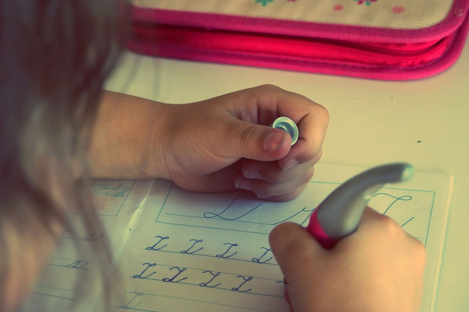 how to get your child to do their homework - little girl practising her handwriting