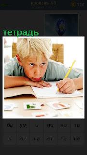 за столом мальчик пишет в тетради ручкой и смотрит вперед