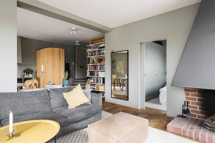 Salón con paredes verdes y sofá gris