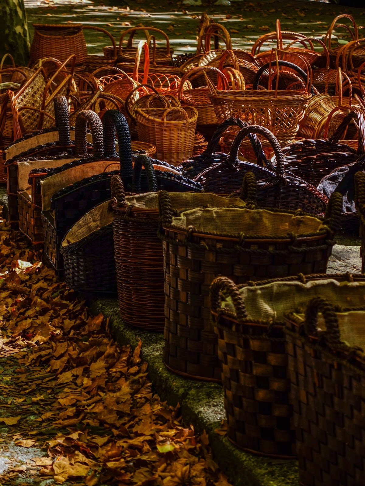 Hand woven willow baskets displayed at a market in Porto, Portugal surrounded by autumn leaves.