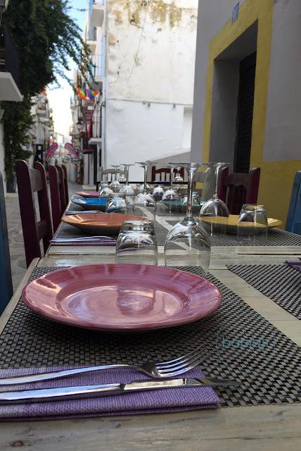 assiettes colorées sur une table de restaurant dans une ruelle du vieil Ibiza