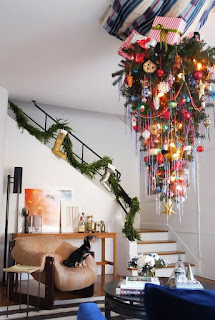 An upside-down Christmas tree hanging in the stairwell of a home